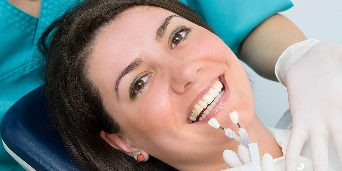 Woman in dental chair with tooth shade guide
